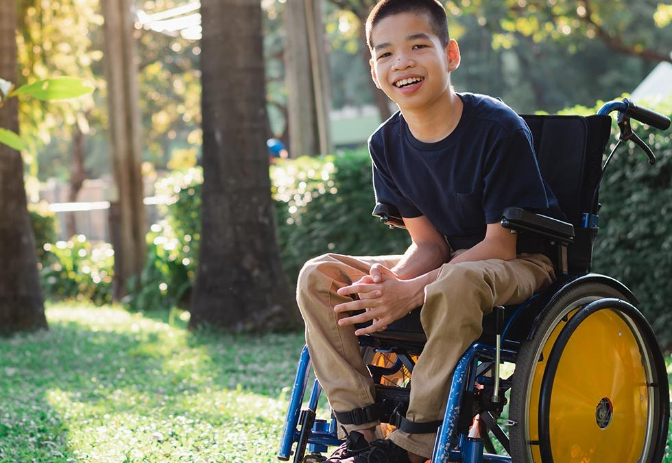young boy in a wheelchair smiling at camera